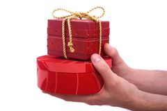Mann bietet rote Geschenkkästen an Stockfotografie
