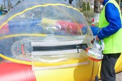 Mann bläst einen großen Ballon für die Wasserfahrten auf Die Einspritzung von Lizenzfreies Stockfoto