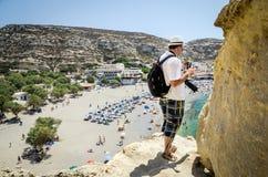 Mann bleibt auf Klippe und dem Aufpassen auf Seebucht von Matala-Stadt auf Kreta-Insel, Griechenland Lizenzfreie Stockfotos