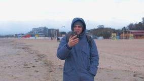 Mann Blogger in einem Blau hinunter Jacke gehend auf den Sandstrand durch das Meer und ein Videoschwätzchen am Handy sprechend stock video footage