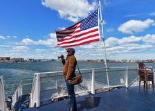 Mann an Boston-Ufergegend und an Staatsflagge MA Vereinigter Staaten Stockbild
