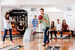 Mann-Bowlingspiel mit dem Freund, der am Verein fotografiert Stockbilder