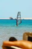Mann bräunt sich auf windsurfing Hintergrund Stockfotografie