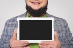 Mann demonstriert den Tablettenschirm in beiden Händen Lizenzfreies Stockbild
