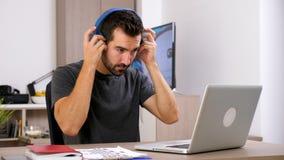 Mann, den Arten auf Computertastatur dann fasten, Kopfhörer auf seinen Kopf setzen stock video footage