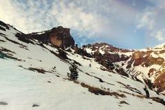 Mann in den Bergen mit Snowboard hinten Stockbilder