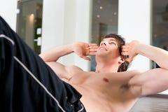 Mann, den das Handeln sitzt, ups in Gymnastik Lizenzfreie Stockfotografie