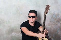 Mann in den Denimkurzen hosen, die nahe bei einer Gitarre auf dem Wandhintergrund in der Artgrunge, Musik, Musiker, Hobby, Lebens Lizenzfreies Stockfoto