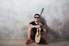 Mann in den Denimkurzen hosen, die nahe bei einer Gitarre auf dem Wandhintergrund in der Artgrunge, Musik, Musiker, Hobby, Lebens Stockfoto