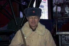 Mann in den durchdachten Militäruniformen wirft für Fotos mit Besuchern der Ausstellung auf Stockfotografie