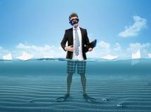 Mann in den Flossen und in den Schutzbrillen übergibt den Ordner, der im Meer steht Stockbilder