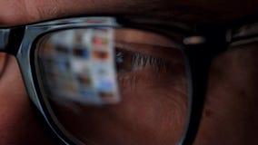 Mann in den Gläsern, die auf dem Monitor und dem surfenden Internet schauen Der Bildschirm wird in den Gläsern reflektiert stock video
