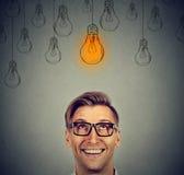 Mann in den Gläsern, die oben Glühlampe der guten Idee über Kopf betrachten Lizenzfreies Stockbild