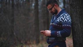 Mann in den Gläsern geht durch den Herbstwald und benutzt Smartphone Langsame Bewegung stock video