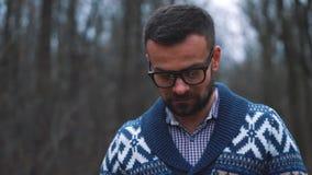 Mann in den Gläsern geht durch den Herbstwald und macht Foto durch Smartphone stock footage