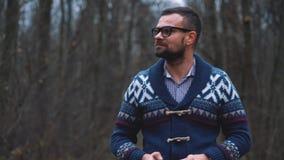 Mann in den Gläsern geht durch den Herbstwald und macht Foto durch Smartphone Langsame Bewegung stock video