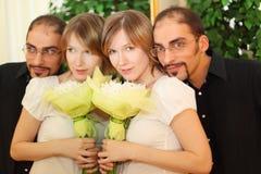 Mann in den Gläsern und im blonden Mädchen der Schönheit mit Blumen Lizenzfreie Stockfotos