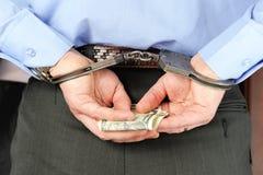 Mann in den Handschellen hält Geld in seinen Palmen hinter seinem zurück Lizenzfreies Stockfoto