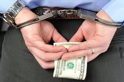 Mann in den Handschellen hält Geld in seinen Palmen hinter seinem zurück Stockfotografie