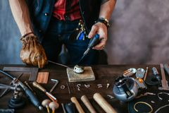 Mann in den Handschuhen, die Silber schmelzen, um Schmuck zu machen stockfotografie