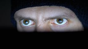 Mann in den Hutblicken auf einen Laptopmonitor nachts stock footage