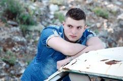 Mann in den Jeans, lehnend auf einem alten beschädigten Fahrzeug Lizenzfreies Stockbild