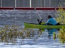 Mann in den kleinen Paddelbootsfischen in den Sumpfgebieten am Cachuma See, Santa Barbara County stockfotografie