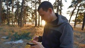 Mann in den Kopfhörern hat Rest und hört Musik während des Hörens Musik auf Kopfhörern auf einem Smartphonebetrieb stock video