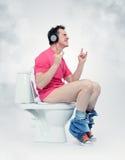 Mann in den Kopfhörern, die auf der Toilette sitzen Stockbilder