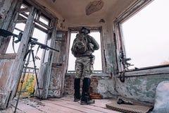 Mann in den Militäruniformblicken aus dem alten Fenster heraus stockfoto