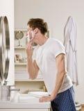 Mann in den Pyjamas beim Badezimmerrasieren Stockfotografie
