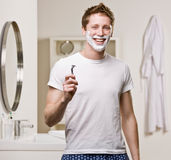 Mann in den Pyjamas beim Badezimmerrasieren Stockbilder