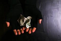 Mann in den schwarzen Handschuhen, die einen Dollarschein auf einem schwarzen Hintergrund halten Stockbild