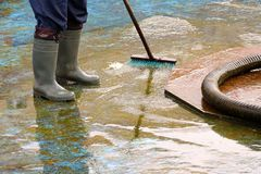 Mann in den Stiefeln säubert nach der Sommersaison die Unterseite des Brunnens lizenzfreie stockfotos