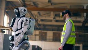 Mann in den VR-Gläsern und ein Cyborg ziehen zusammen um stock video footage