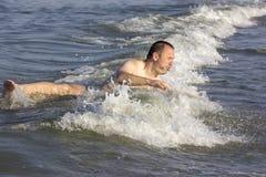 Mann in den Wellen Stockbild