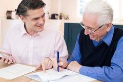 Mann, der älterem Nachbar mit Finanzschreibarbeit hilft stockbilder