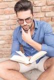 Mann, der über das Ende des Buches sich wundert, das er liest Lizenzfreie Stockfotografie