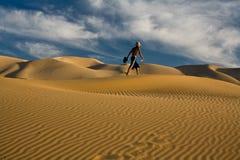 Mann, der über den Wüstendünen wandert Lizenzfreie Stockfotografie
