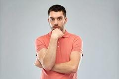 Mann, der über grauem Hintergrund denkt Lizenzfreie Stockfotos