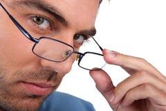 Mann, der über seinen Gläsern blickt Lizenzfreies Stockfoto