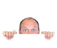 Mann, der über weißem Rand lugt lizenzfreie stockfotografie
