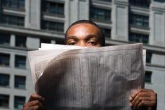 Mann, der über Zeitung schaut Stockfotos