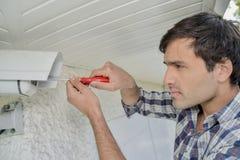 Mann, der Überwachungskamera repariert stockbilder