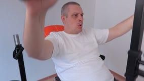 Mann, der Übung auf Übungsmaschine tut stock video footage