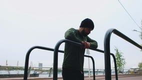 Mann, der Übung für ABS im Park tut Junger athletischer Mann gekleidet in der Sportkleidung, Übung auf Stangen, in tuend stock video