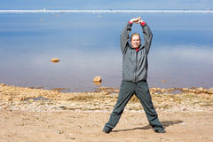 Mann, der Übungen auf dem Sand tut Lizenzfreies Stockfoto