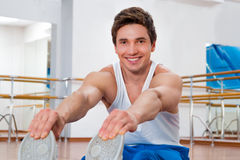 Mann, der Übungen in der Turnhalle ausdehnend tut Lizenzfreies Stockfoto