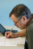 Mann, der 1040 Bundeseinkommensteuer-Formular tut Stockbild