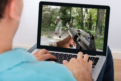 Mann, der Actionspiel auf Laptop spielt lizenzfreie stockfotografie